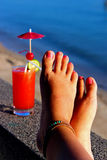 Leg selfie with red cocktail on background. Alcohol red cocktail with with cherry, ice and lime by the water Stock Image