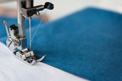 The leg of the sewing machine with a needle sews blue fabric. royalty free stock photo