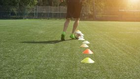 Leg skill training on football field. Soccer player running in football field leading ball between cones. Leg skill training on football field. Low angle view of stock footage