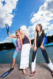 Leg-split. Three happy young caucasian girlfriends standing together on the yacht dock and smiling royalty free stock photography