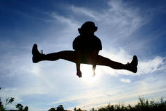 Leg split silhouette jump. Silhouette of person jumping and leg split in air with blue sky and clouds Royalty Free Stock Images
