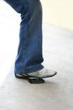 Leg steping cellphone Stock Photos