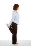 Leg stretch. Pretty brunette standing on one leg doing a quadriceps stretch Royalty Free Stock Photos
