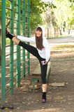 Leg stretching. Beautiful brawny young sport woman wearing sport clothes hoodie, trainers, leggins and stretching her legs near vertical sport bar outdoors in Stock Photos