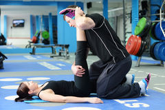 Leg stretching with personal trainer Stock Images