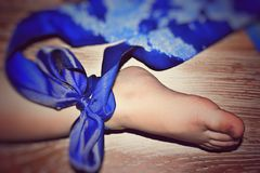 The leg of the sweet boy. The leg of the sweetest boy with a blue ribbon on a wooden background Royalty Free Stock Image