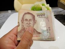 Leg Thaise bankbiljetten voor betaling voor - Bankbiljet 1000 Baht Thaise in hand, Koning Rama 9 op het Thaise geld stock foto's