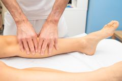 Leg treatment of an athlete by a physiotherapist stock photo