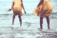Leg of two asian little child girls jumping and playing on beach. Together in summer vacation in vintage color tone stock photo