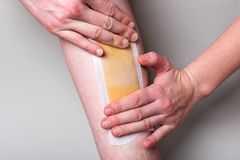 Leg waxing. Removing hair from legs on gray background. royalty free stock photos