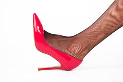 Leg wearing heel shoe. Red footwear with gloss. Femininity and attractiveness. How to emphasize beauty Royalty Free Stock Photography