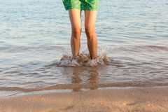 Leg of woman running on beach with water splashing. summer vacation. legs of a girl walking in water on sunset.  stock photography
