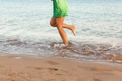 Leg of woman running on beach with water splashing. summer vacation. legs of a girl walking in water on sunset.  royalty free stock photos