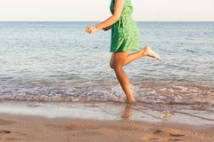 Leg of woman running on beach with water splashing. summer vacation. legs of a girl walking in water on sunset.  stock images