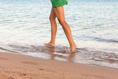 Leg of woman running on beach with water splashing. summer vacation. legs of a girl walking in water on sunset.  stock photo