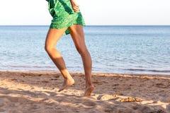 Leg of woman running on sand beach. summer vacation. Happy beautiful woman running on the beach stock photos