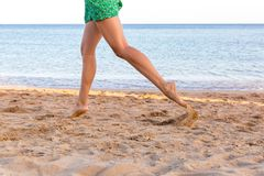 Leg of woman running on sand beach. summer vacation. Happy beautiful woman running on the beach stock photo