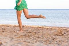 Leg of woman running on sand beach. summer vacation. Happy beautiful woman running on the beach stock images