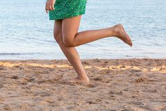 Leg of woman running on sand beach. summer vacation. Happy beautiful woman running on the beach royalty free stock photography