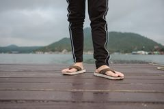 Leg of woman wearing sandal stand alone on wooden bridge has riv. Leg of young woman wearing sandal stand alone on wooden bridge has river, mountain, sky are Stock Photos