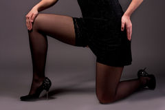 Leg of young pretty female. Standing on knees isolated on gray stock photography