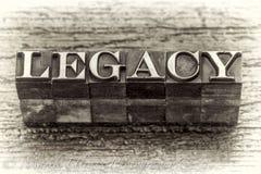 Legacy word in letterpress metal type. Legacy word in vintage metal type printing blocks over grunge wood, black and white image royalty free stock photos