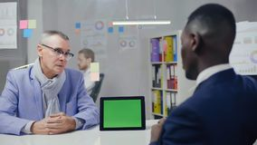 Legal advice agency office. Afro american lawyer. Talking his caucasian client about customer`s rights stock footage
