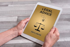Legal advice concept on a tablet. Female hands holding a tablet with legal advice concept Stock Photos