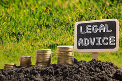 Legal Advice - Financial opportunity concept. Golden coins in soil Chalkboard on blurred urban background.  Stock Images