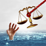 Legal Aid Concept. And law help or lawyer services concept as a justice scale being offered to save a drowning person as a symbol of attorney services solving Royalty Free Stock Images