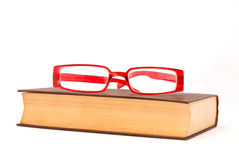 Legal book. An old yellowed legal book with modern trendy red eyeglasses on top. Image isolated on white studio background Stock Image