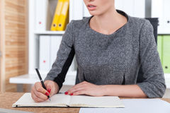 Legal company employee is making notes. Close up of office employee with slightly open mouth making notes in her notebook. Concept of legal work and paperwork Royalty Free Stock Image
