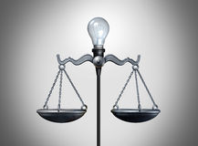 Legal Idea. And smart intelligent law strategy concept as an illuminated lightbulb balancing a justice scale as a bright lawyer or attorney icon for legislation Stock Image