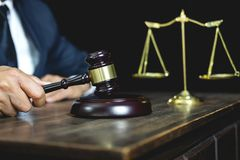 Legal law, advice and justice concept, male lawyer or notary working on a documents and report of the important case and wooden. Gavel, balance on table in royalty free stock photography