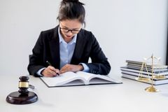 Legal law, advice and justice concept, Professional Female lawyers working on courtroom sitting at the table and signing papers w. Ith gavel and Scales of stock images