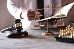 Legal law, advice and justice concept, Professional male lawyers. Working on courtroom sitting at the table and signing papers with gavel and Scales of justice stock photo