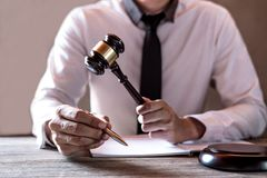 Legal law, advice and justice concept, Professional male lawyers. Working on courtroom sitting at the table and signing papers with gavel and Scales of justice royalty free stock image