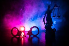 Legal law concept. Silhouette of handcuffs with The Statue of Justice on backside with the flashing red and blue police lights at. Foggy background. Selective royalty free stock photos