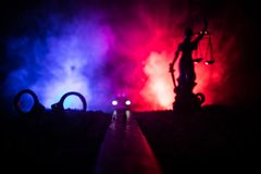 Legal law concept. Silhouette of handcuffs with The Statue of Justice on backside with the flashing red and blue police lights at. Legal law or crime concept royalty free stock photography
