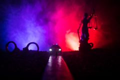 Legal law concept. Silhouette of handcuffs with The Statue of Justice on backside with the flashing red and blue police lights at. Legal law or crime concept stock image