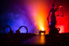 Legal law concept. Silhouette of handcuffs with The Statue of Justice on backside with the flashing red and blue police lights at. Legal law or crime concept stock photos