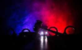 Legal law concept. Silhouette of handcuffs with The Statue of Justice on backside with the flashing red and blue police lights at. Legal law or crime concept stock photo