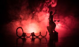 Legal law concept. Silhouette of handcuffs with The Statue of Justice on backside with the flashing red and blue police lights at. Foggy background. Selective royalty free stock photography