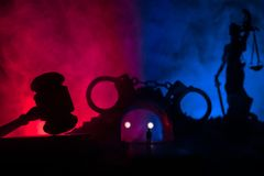 Legal law concept. Silhouette of handcuffs with The Statue of Justice on backside with the flashing red and blue police lights at. Legal law or crime concept royalty free stock photo