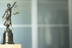 Legal law firm statue. Legal law firm bronze statue of the goddess themis with scales of justice in attorneys office Stock Image