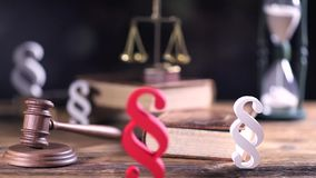 Legal office. Attorney at law. Judge gavel, books, scale of justice and paragraph sign on bokeh background. Dolly shot