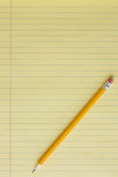 Legal Pad. Blank yellow lined legal pad with yellow number 2 pencil placed at a diagnal.  Portrait orientation Stock Photo