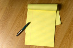 Legal Pad and Pen. A blank, yellow legal pad on a brown wooden desk or floor with a writing pen on the edge, add your own copy Stock Photos