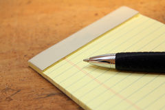 Legal pad with pen. On wood background Stock Images