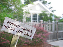 Legal series. Leaning home for sale real estate and foreclosure sign in front of a modern single family home Stock Photos